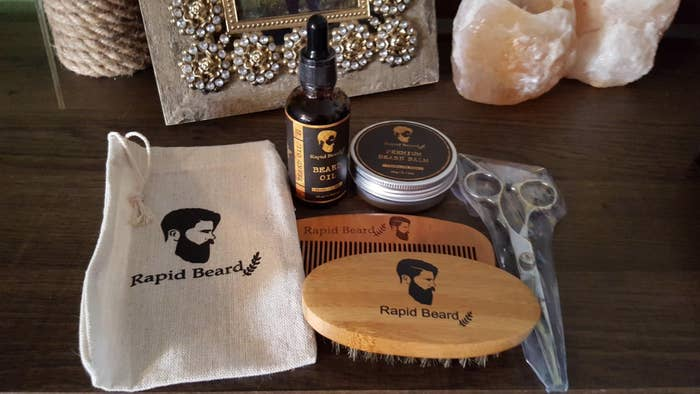 """Promising review: """"My husband is a beard man (lol), and I got him this kit as a gift. He absolutely loved it. He loves the oil. Whenever he goes to the barber, she always puts an oil in his beard and he's been wanting one for months now so I'm super happy he was so pleased! It comes in a black box with a comb, brush, scissors, balm, and a little burlap style storage bag!"""" —Allie and AbelGet it from Amazon for $34.97."""