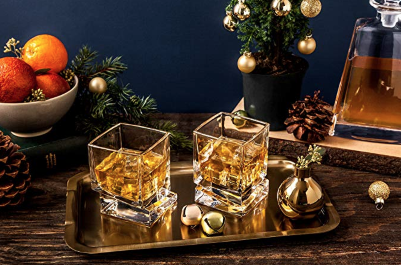 Two glass whiskey glasses with a bottom that's shifted to the side