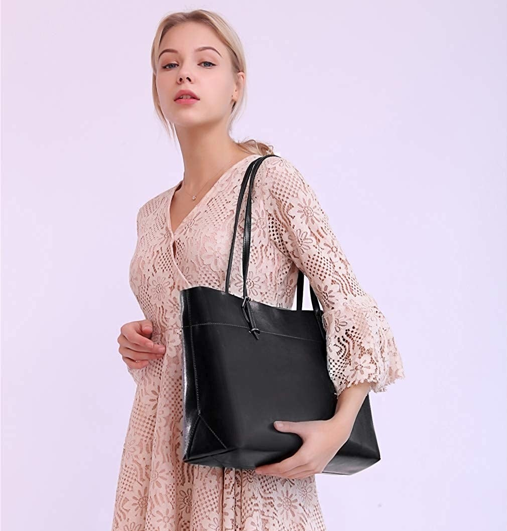 Model with the black rectangle-shaped tote bag over their shoulder