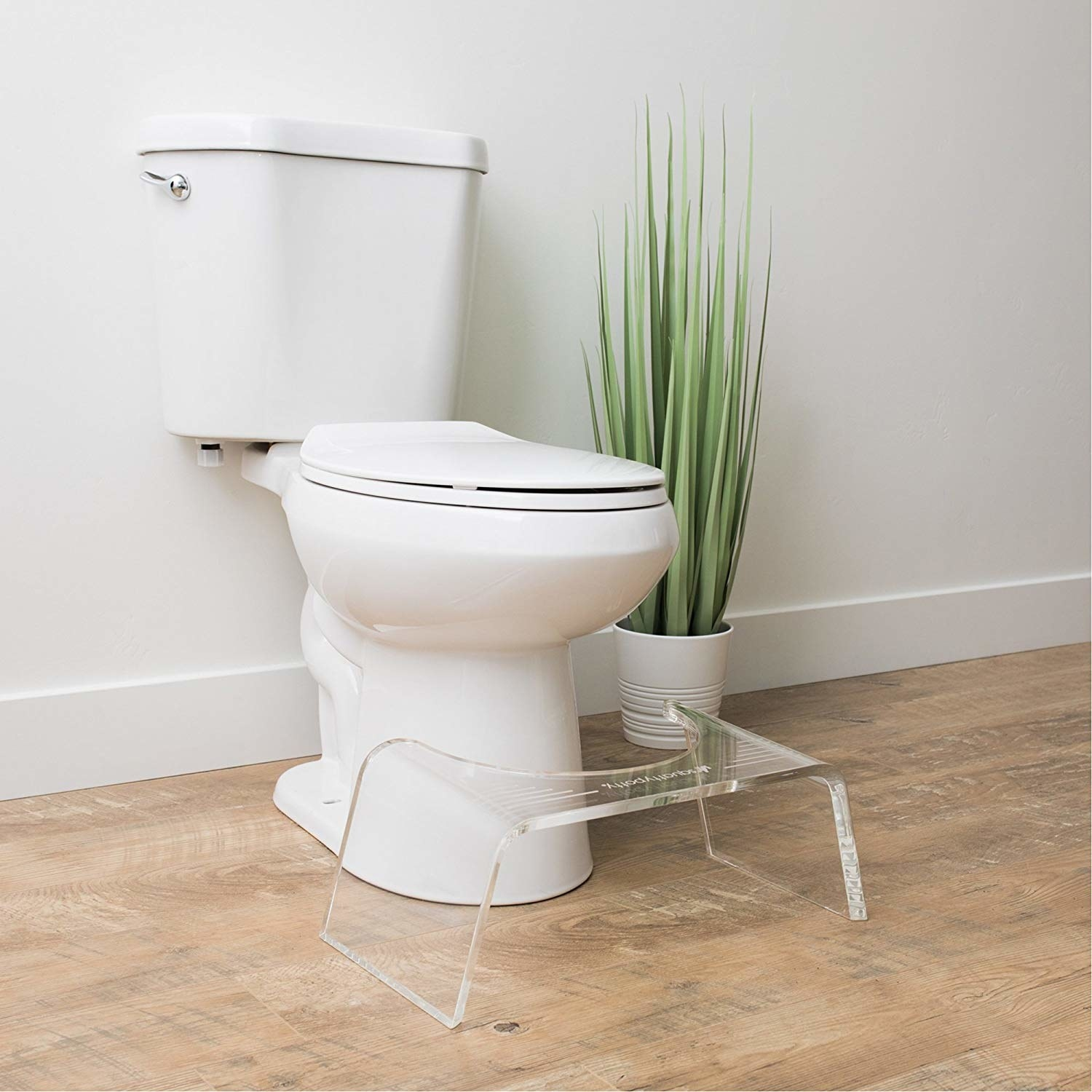 The clear step stool with a rounded side against a toilet