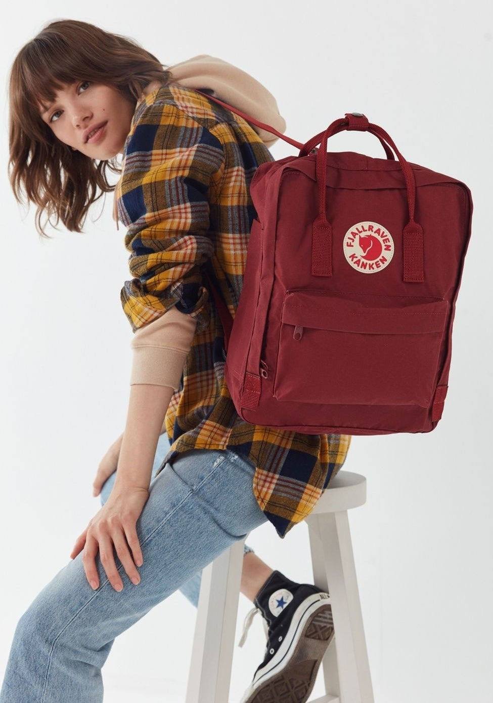 Model with the rectangle-shaped backpack with top handles, and a big front zippered pocket in red