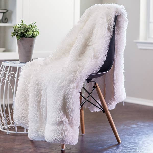 The fuzzy blanket in white sitting on a chair