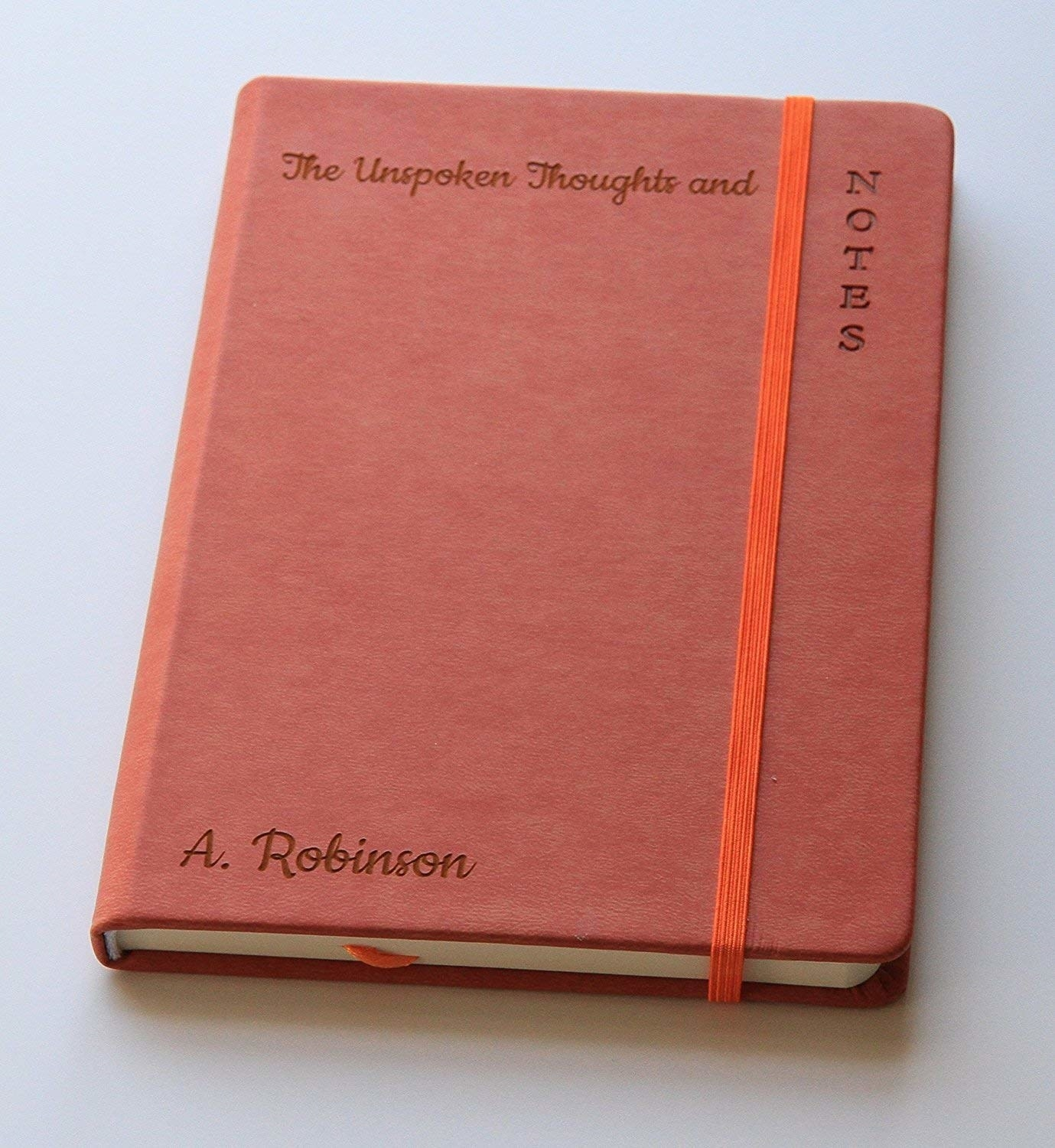 moleskine-like notebook that has an engraved name
