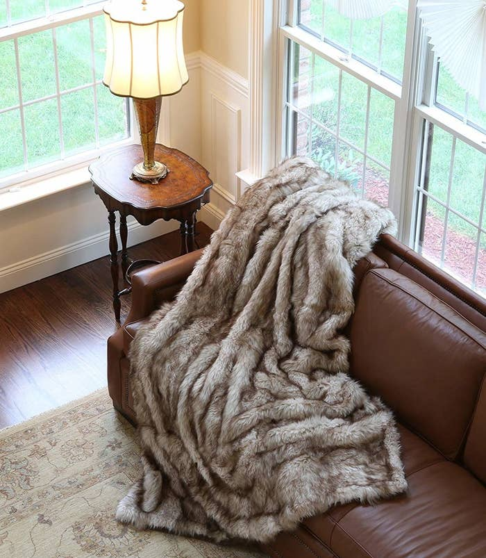 The faux fur blanket draped over a couch, in a white and brown blend
