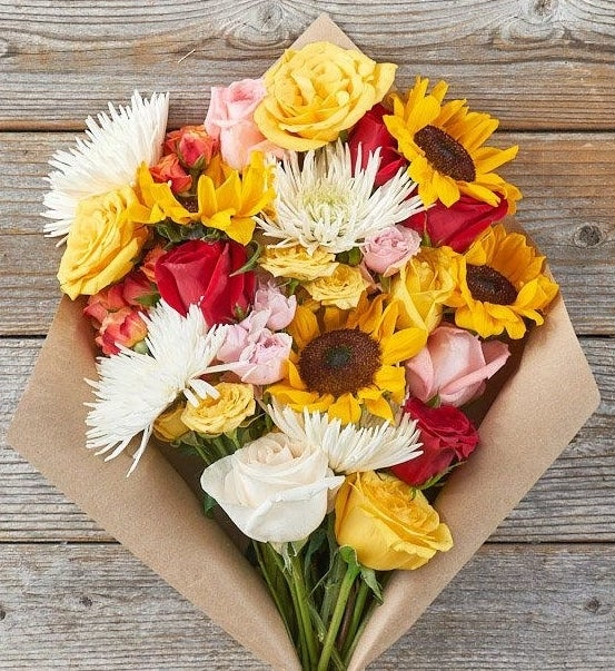 A bouquet of roses, spider mums, and sunflowers