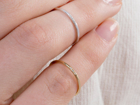 A hand with the bands in gold and white gold