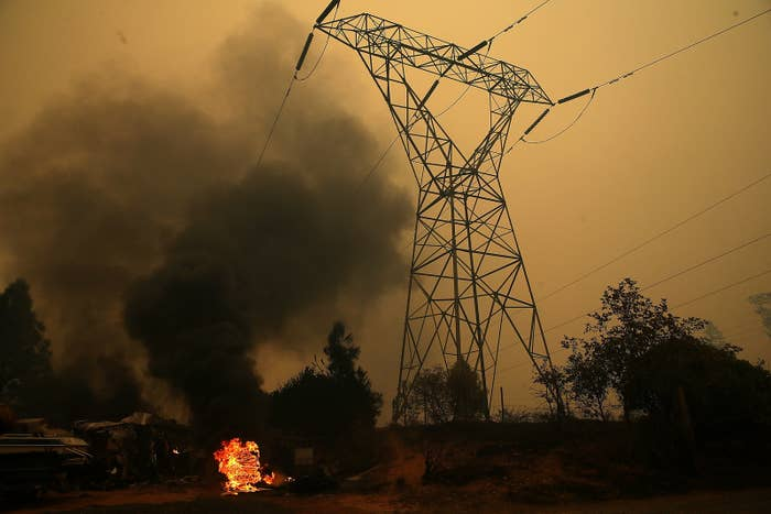 Smoke rises next to a power line tower after the Camp fire in Big Bend, California.