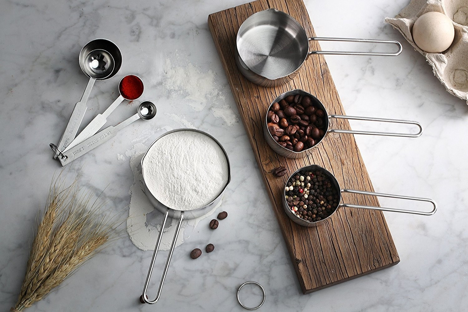A set of stainless steel measuring cups filled with baking ingredients