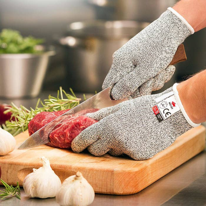 Model wearing grey gloves while cooking meat
