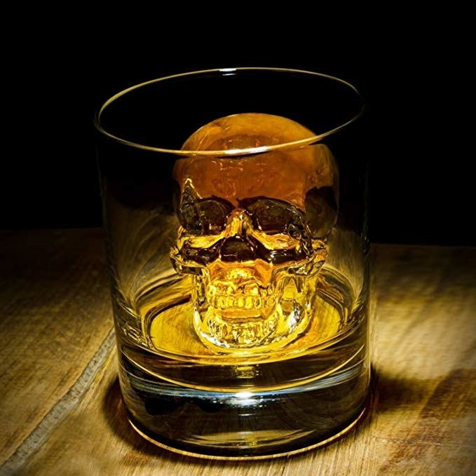 a skull-shaped ice cube made from the mold resting inside a glass