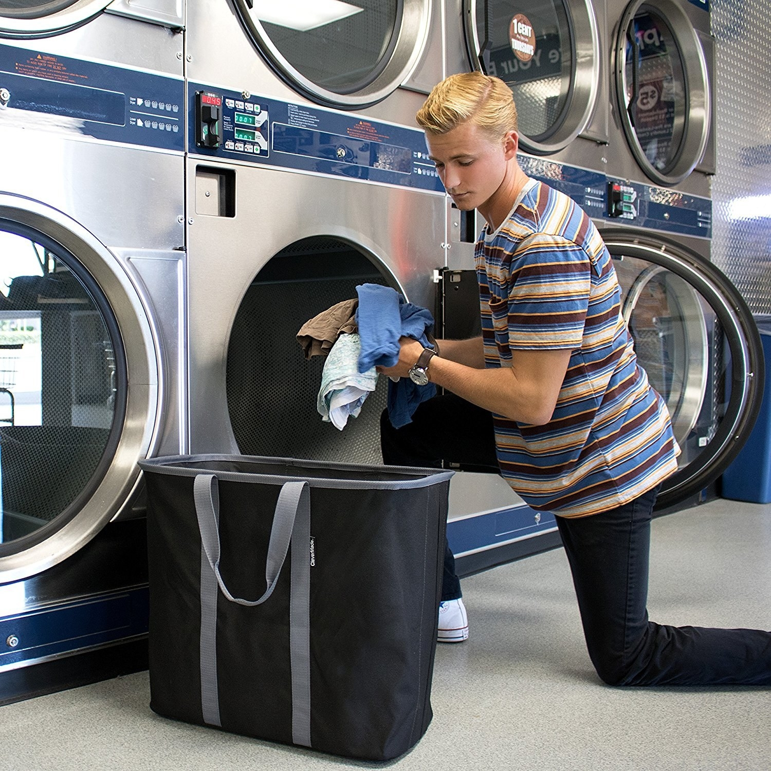 person pulling stuff from the laundry tote to put in a washer in a laundromat