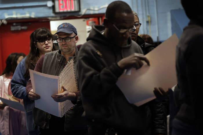 Voters read their ballot papers in Brooklyn on Election Day.