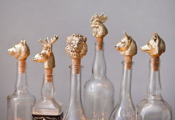 Wine stoppers that are sculpted in different animal heads and stuck in bottles