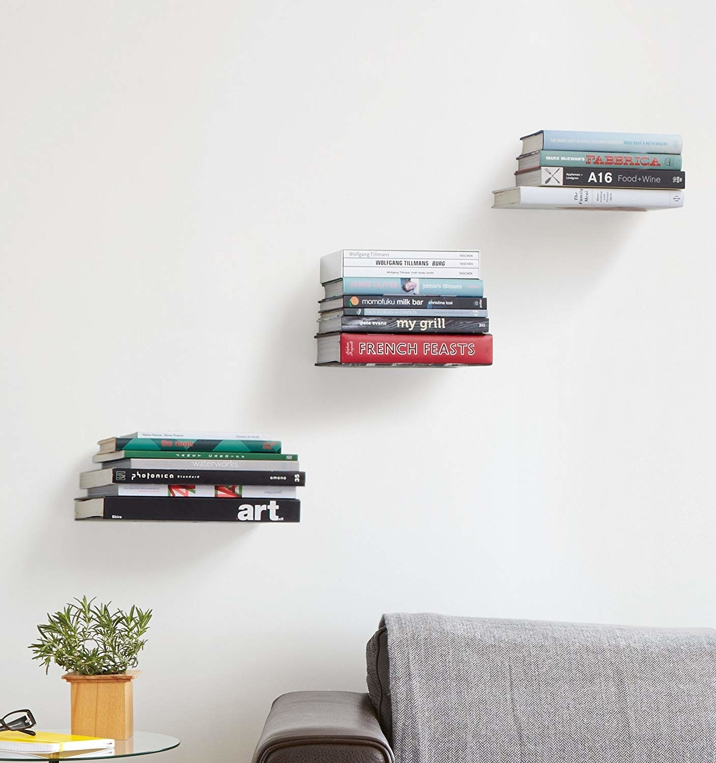 three stacks of books seeming to float on the wall above a couch