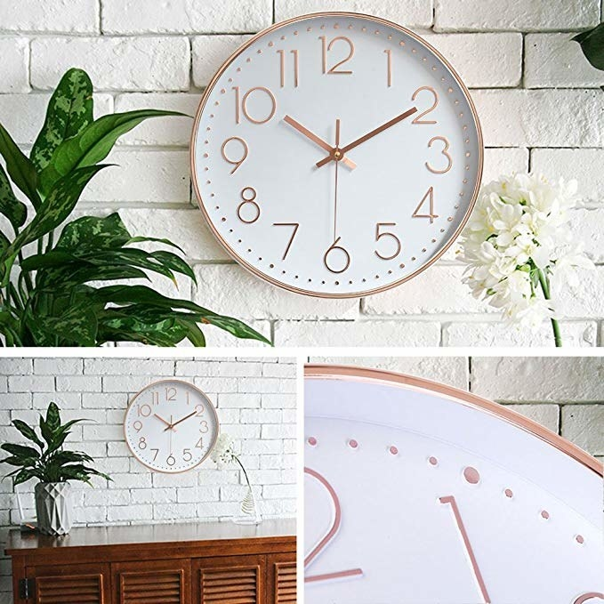 Clock hung up on wall. It has rose gold numbers that are large