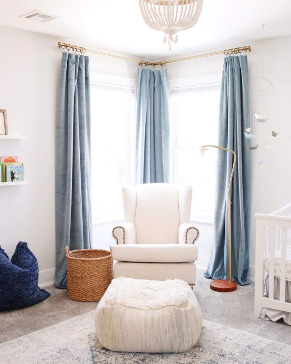 Reviewer's nursery corner windows hung with three floor-to-ceiling blue velvet curtains