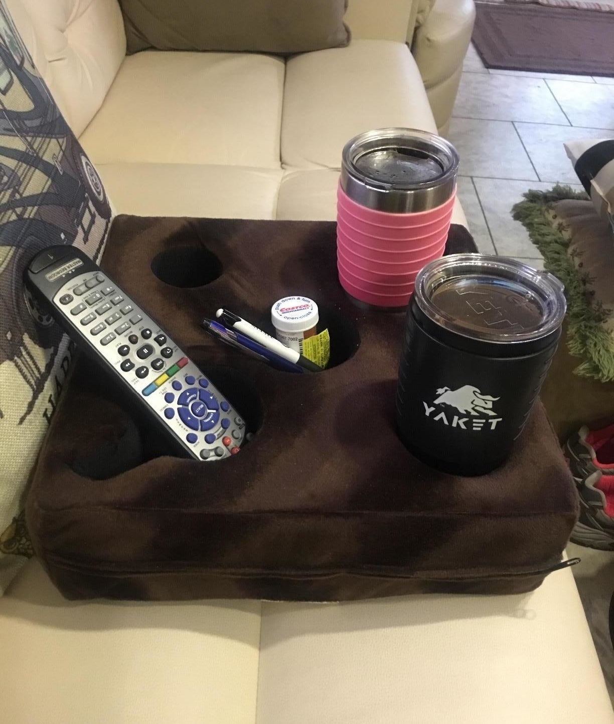 "Promising review: ""The dog can jump up and down and run around the couch — this cup holder holds our drinks in place (just beware if your drink is very full, you'll obviously still get some spillage, so sip some down if pets and kids are around). It holds so many drinks, and BONUS, we have not lost our Apple remote since getting this thing thanks to the middle holder. Before it used to constantly slide through cracks in the couch cushions and sometimes I'd have to use my remote app on my phone for days before finding it. All in all, this Couch Cozy is good for the couch, floor, outdoors.. pretty much anywhere you need it, it works!"" —Jillian R.Get it from Amazon for $34.98."