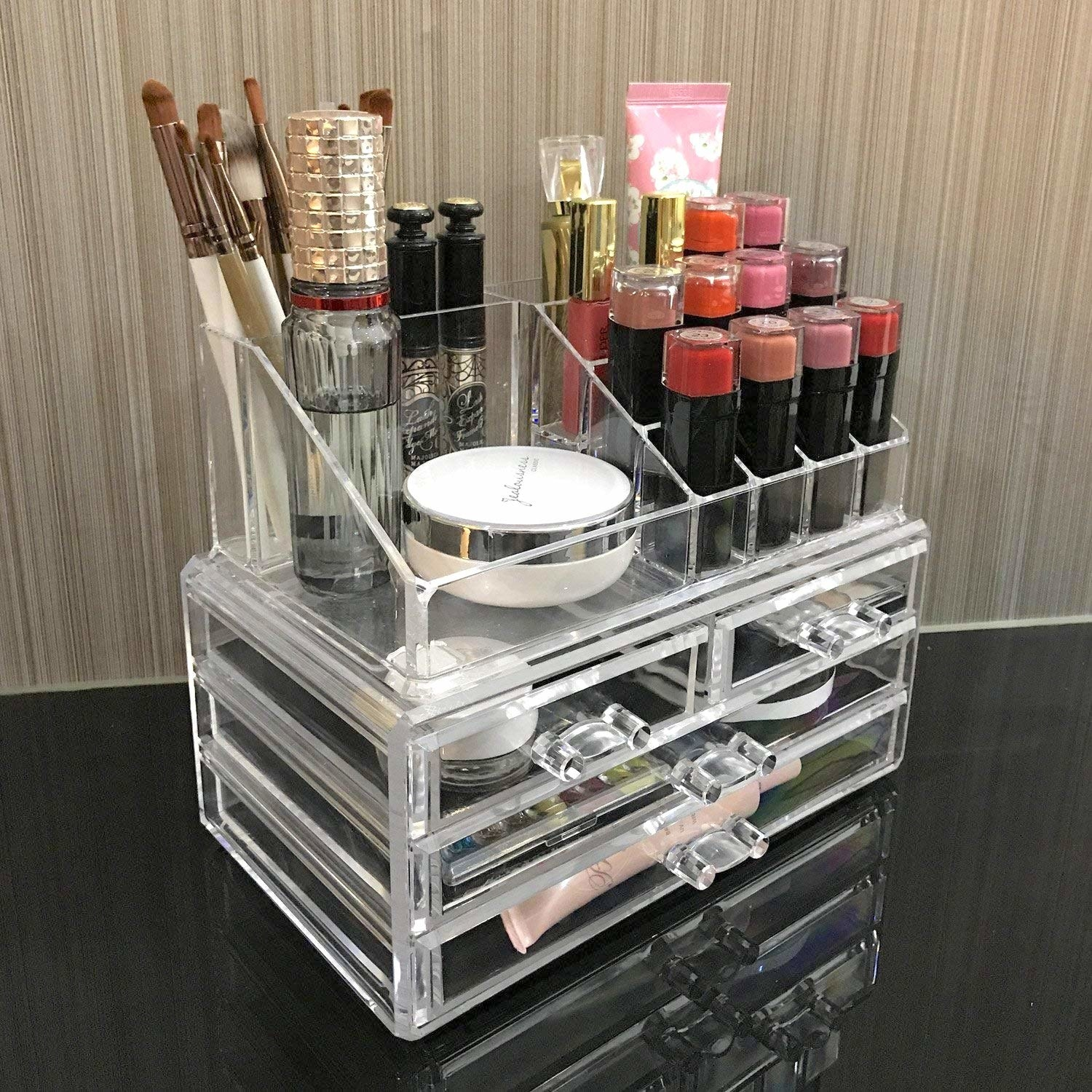 clear organizer with three rows of bottom drawers and slotted lipstick and other storage on top