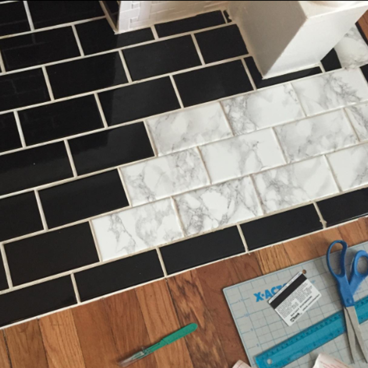 A reviewer's black tile with a few covered in the grey and white paper so they look like marble