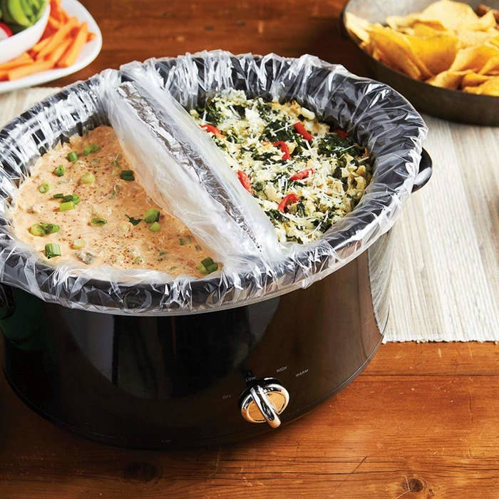 slow cooker with two plastic liners separating two different kinds of dip