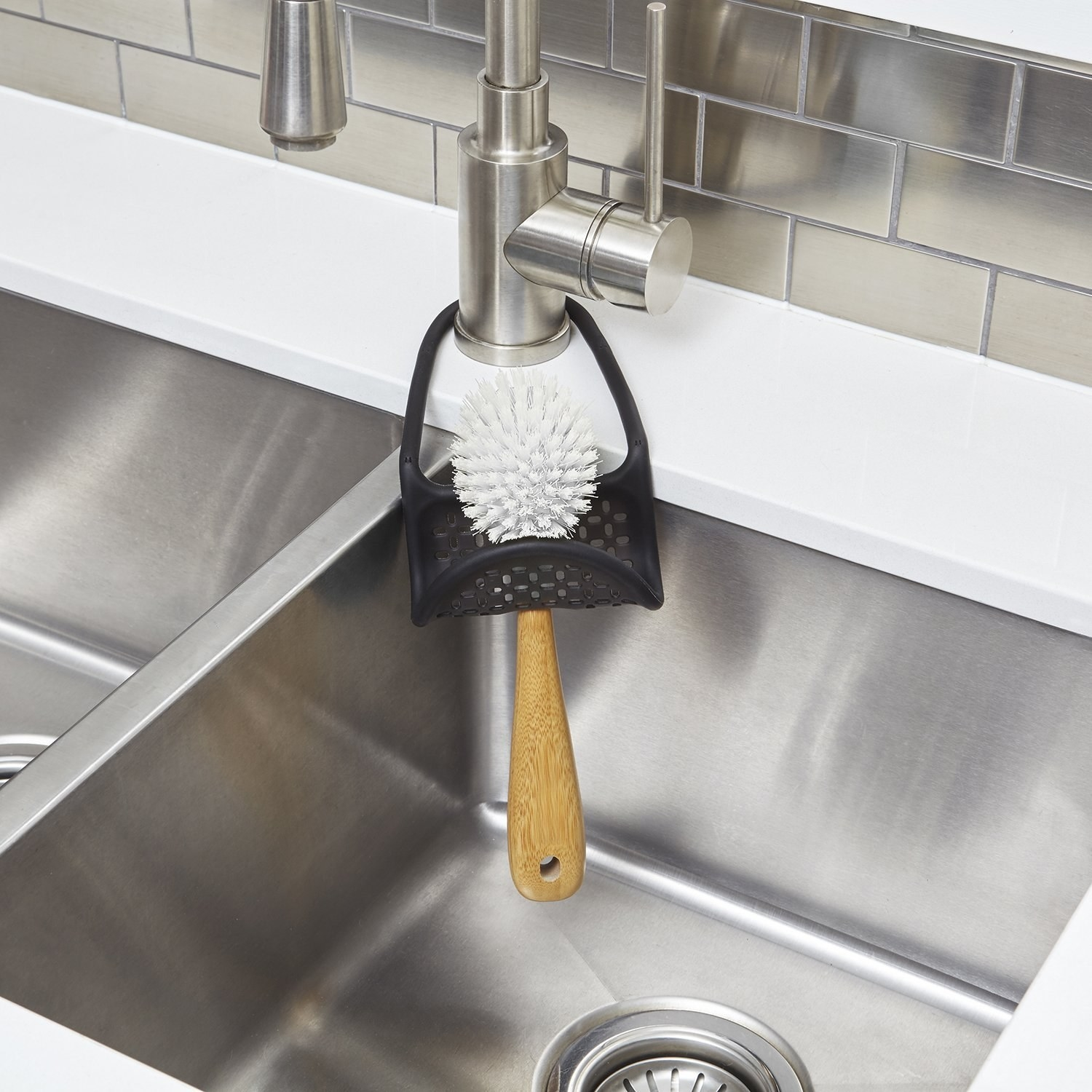the sling-like caddy around the kitchen sink faucet holding a dish brush