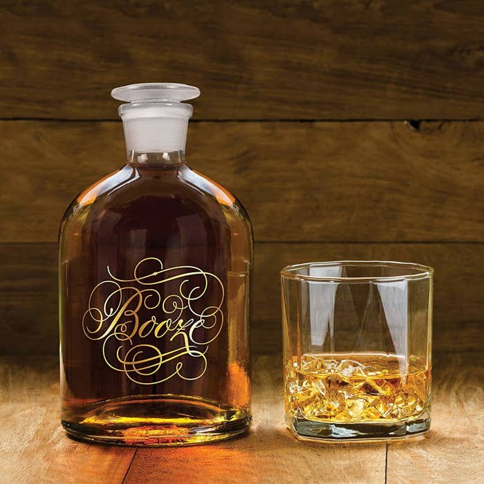 """Glass decanter with the word """"booze"""" printed on it in gold script with lots of flourishes"""