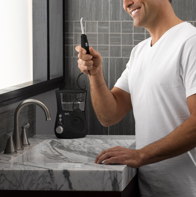 Model smiling while holding a water flosser