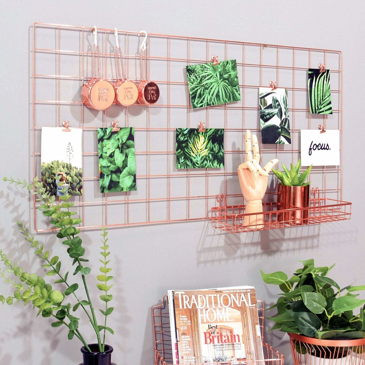 the large organizer on a wall, with 7 postcards clipped to it, and three measuring cups hung on it with s-hooks
