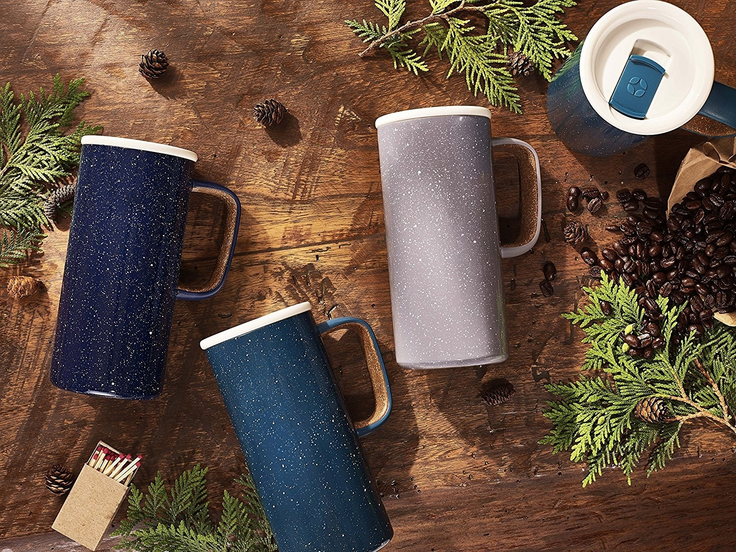 three tall ceramic travel mugs with handles and lids
