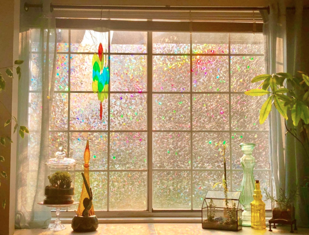 A reviewer's big window covered in the film; the sunlight coming through causes the film to shine lots of different iridescent colors