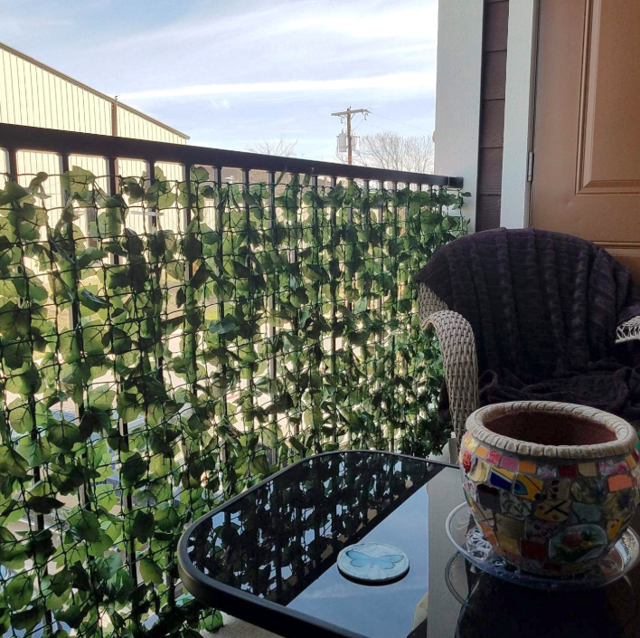 A reviewer's balcony with the ivy hung; it comes on a (rolled-up) plastic grid with the leaves all over it. You can just barely make out a car on the other side, the leaf coverage is so good