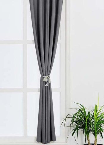 the curtains tied to the side in grey