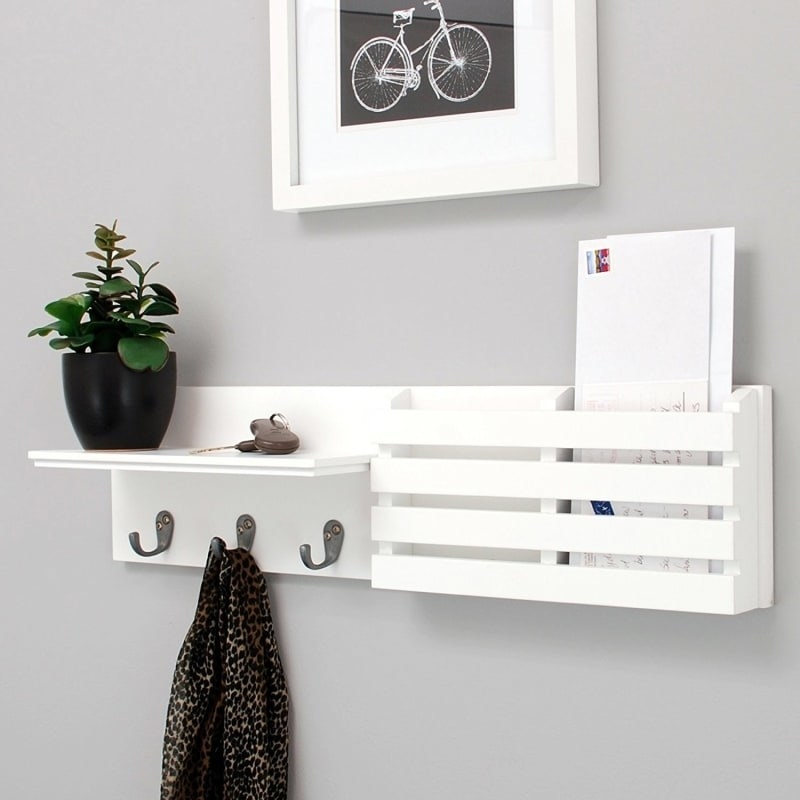 The shelf; it has two horizontal halves: one with a shelf on the top and three hooks right beneath it; the other with two deep-ish slots for letters or other mail
