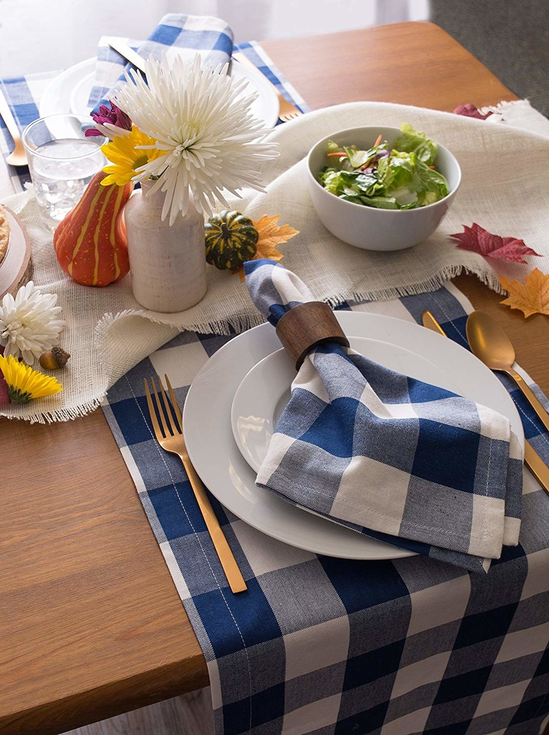 A table set with a wide gingham check table runner in navy and white