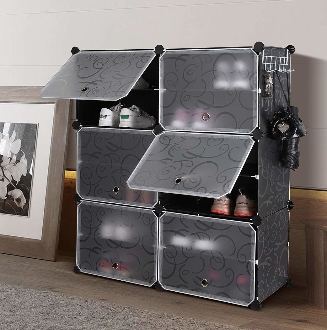A plastic shoe cabinet in grey; six cubbies hold about four pairs of shoes each, each cubby is covered by a translucent panel on a hinge