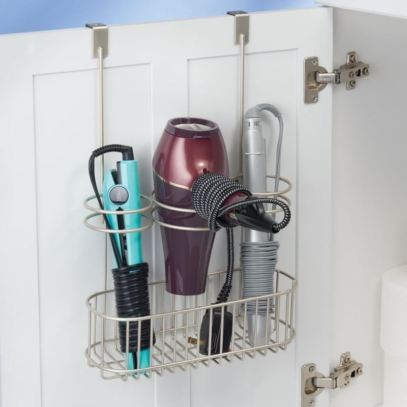 The over-cabinet-door organizer, with a basket on the bottom and three metal circles about five inches above the top of the basket with a straightener, hair dryer, and curling iron set into each