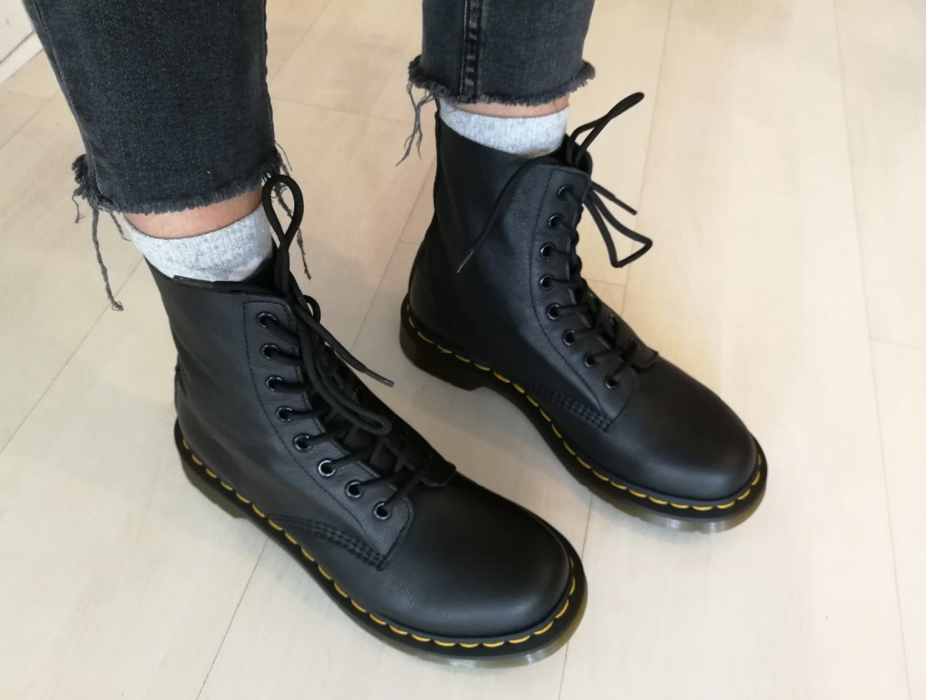 Reviewer wearing the lace-up boots with yellow stitching around the sole