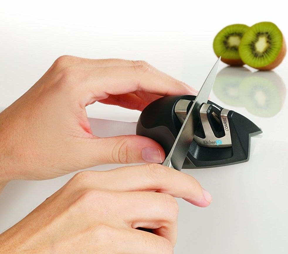 hands using the black sharpener on a knife