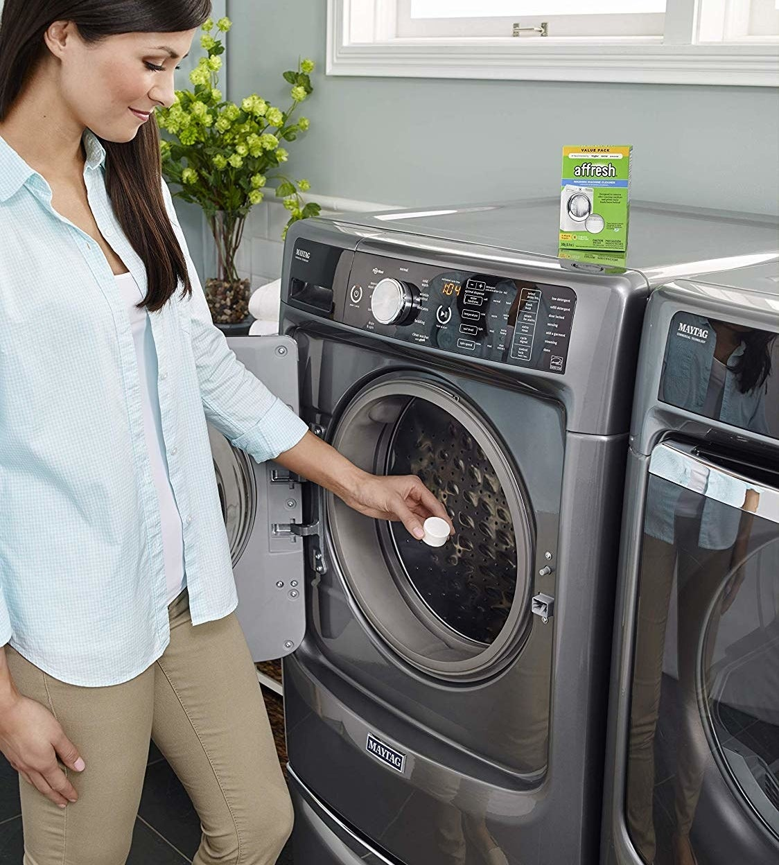 a hand holding a tablet above a washing machine