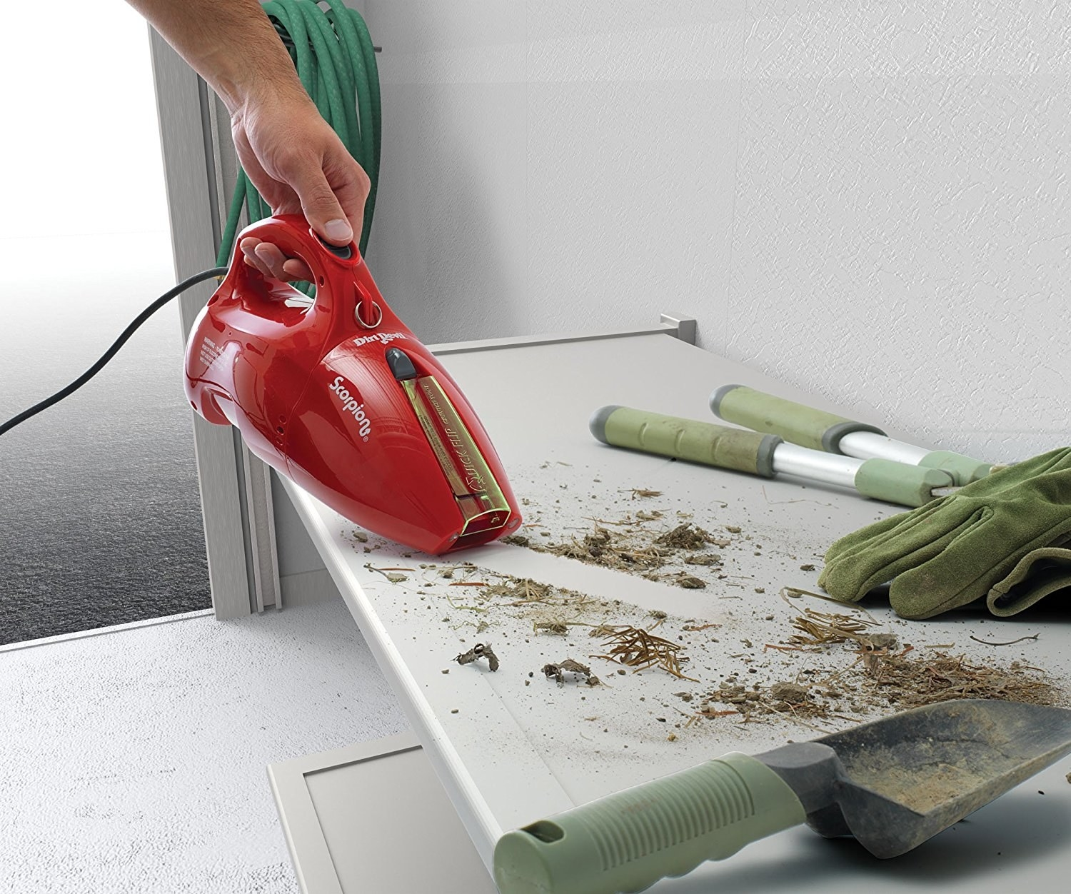 The corded handheld vac being used on soil