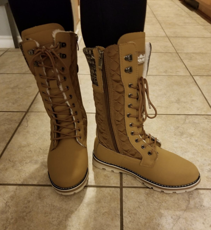 reviewer wearing the mid-thigh length lace-up boots in brown with a zipper along the inner side
