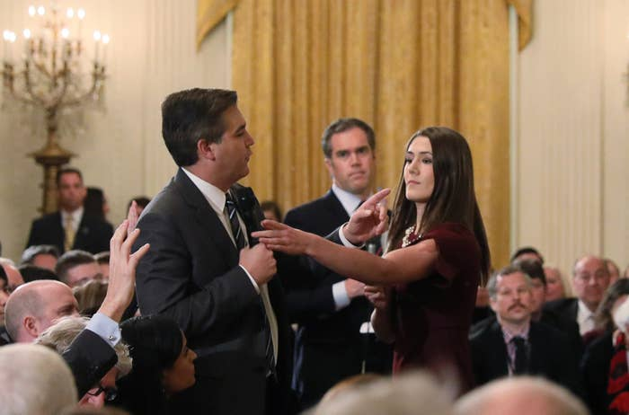 A White House intern tries to take away the microphone held by CNN correspondent Jim Acosta as he questions the president on Nov. 7.