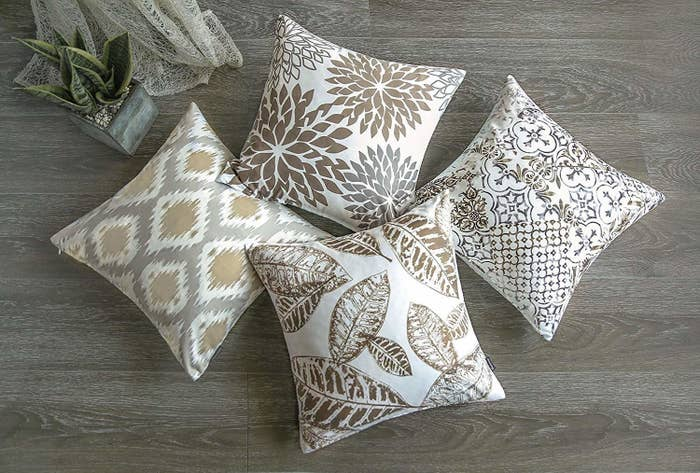 four pillows in white with grey and brown ikat, floral, leaf, and trellis prints on them, respectively