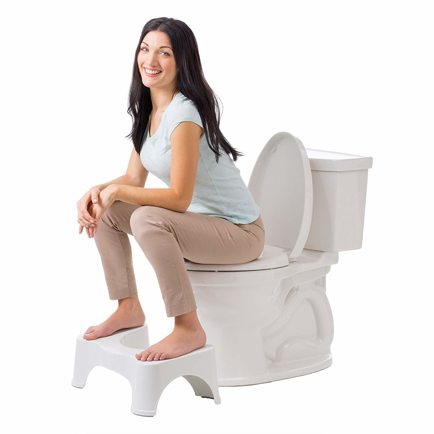 Fully clothed model sits on toilet with their feet on the stool, raising their knees above their hips