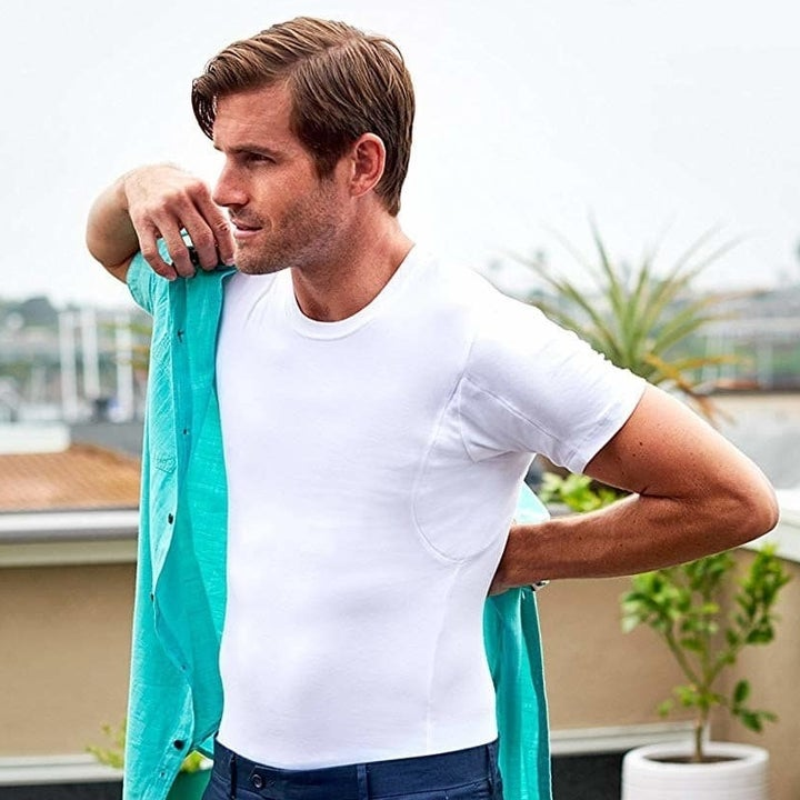Model putting dress shirt over the white undershirt