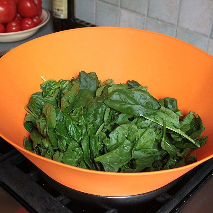Spinach cooking down in a pan; the frywall keeps it all contained