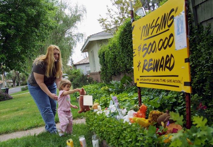 Brandi Dessayer helps her daughter Danielle Dessayer place a stuffed animal outside Laci and Scott Peterson's home on April 15, 2003, in Modesto, California.