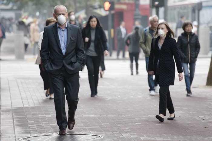 Pedestrians wear masks during their commute in San Francisco on Thursday.