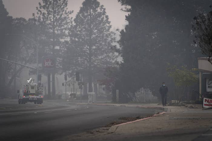 A man wearing a disposable particulate respirator walks along Skyway Road in Paradise, California, on Thursday.