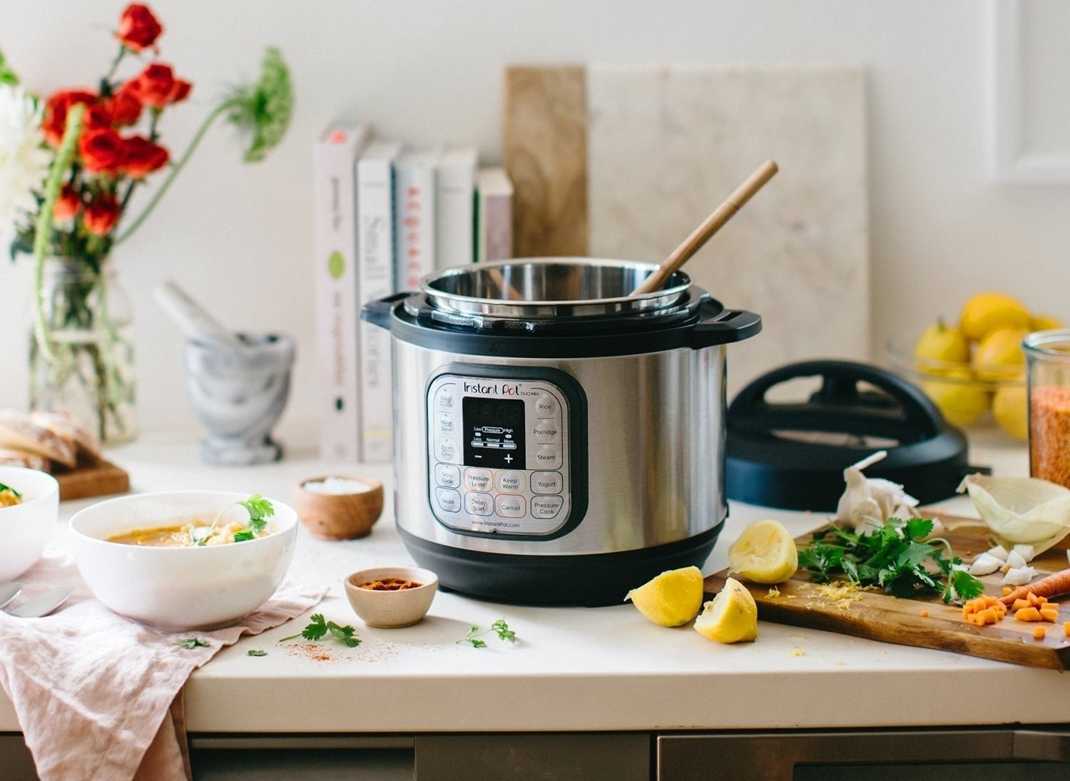 An instant pot on a counter with a wooden spoon and scattered ingredients